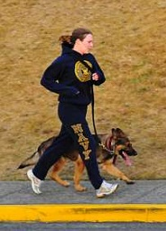 YOKOSUKA, Japan (Feb. 8. 2011) - Master-at-Arms 3rd Class Kendahl Peterson, a K-9 handler with the Military Working Dog Kennel at Commander Fleet Activities Yokosuka, runs with Donci, her K-9 partner. Peterson has been training Donci to become a patrol explosives military working dog for the past two months. (U.S. Navy photo by Mass Communication Specialist Seaman Apprentice Declan Barnes)